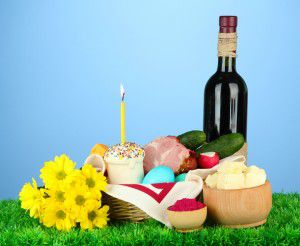 Easter basket: Conceptual photo of traditional easter food in wicker basket, on green grass, on color background
