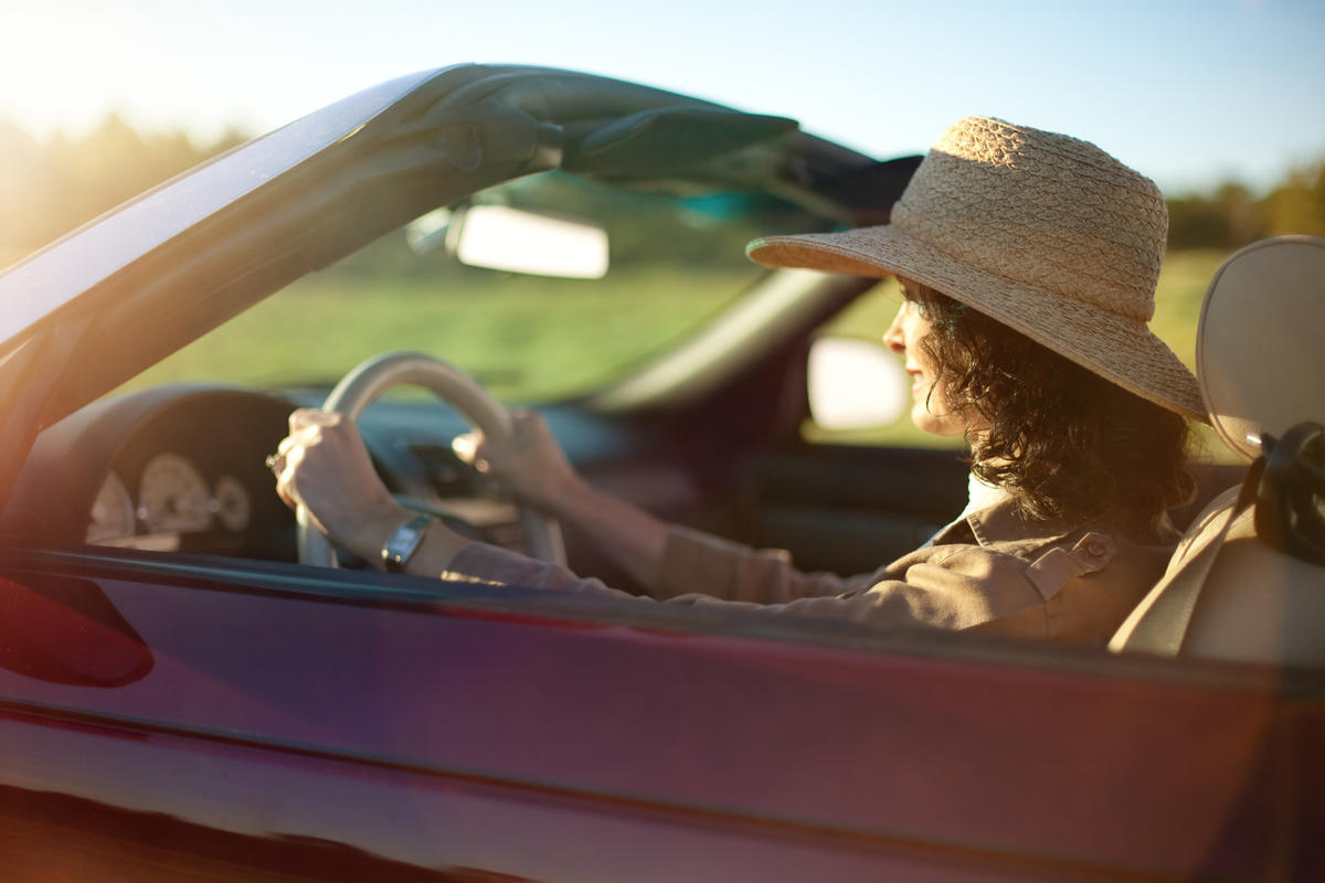 Woman driving convertible automobile on a sunny day in the fall