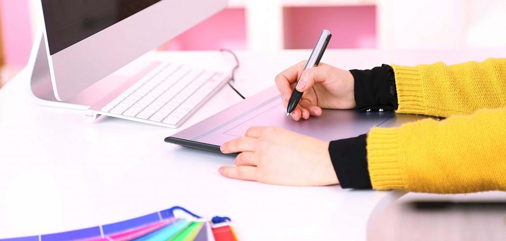Young woman graphic designer working using pen tablet in