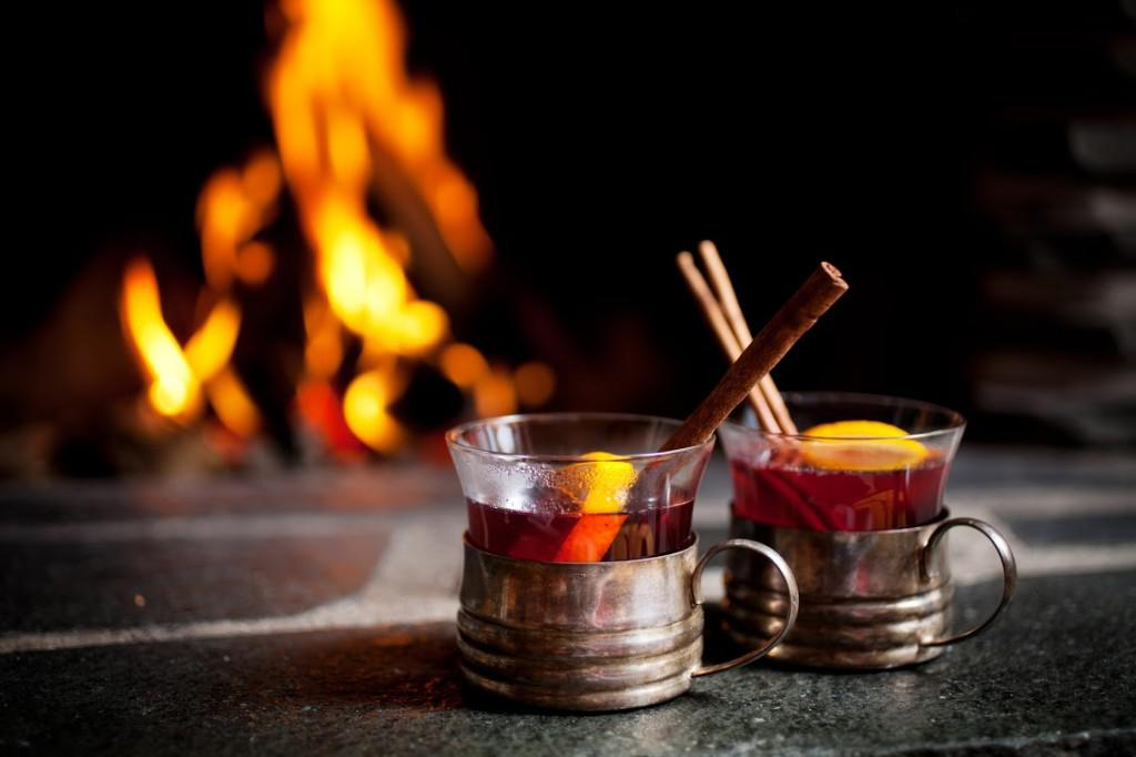 Mulled wine with cinnamon stick by the fireplace