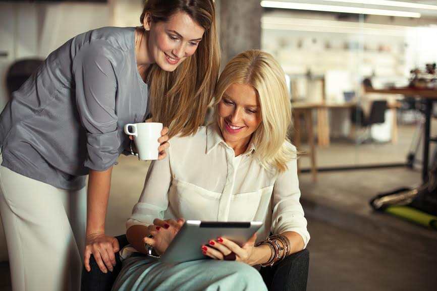 Two smiling businesswomen watching something on a digital tablet.