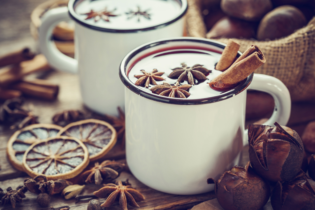 Mulled wine in mugs, dry fruits and chestnuts
