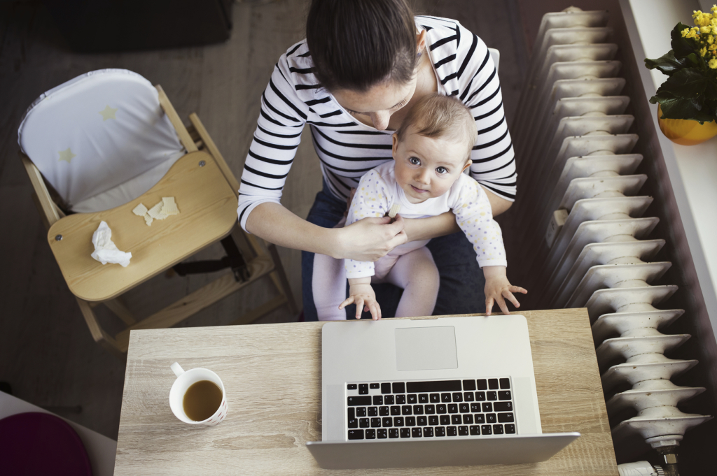 Overhead view of young mother working on computer with baby