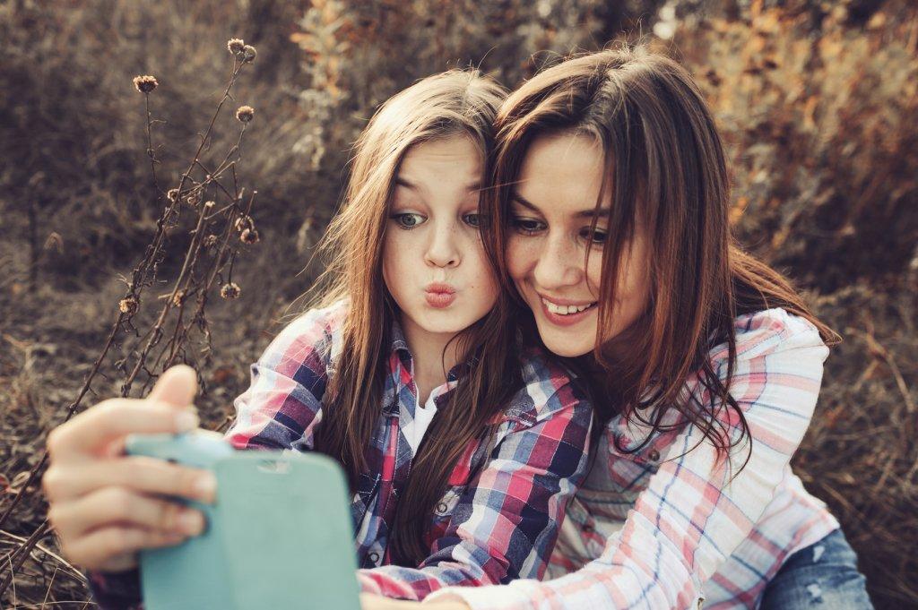 happy mother and daughter making selfie outdoor in summer
