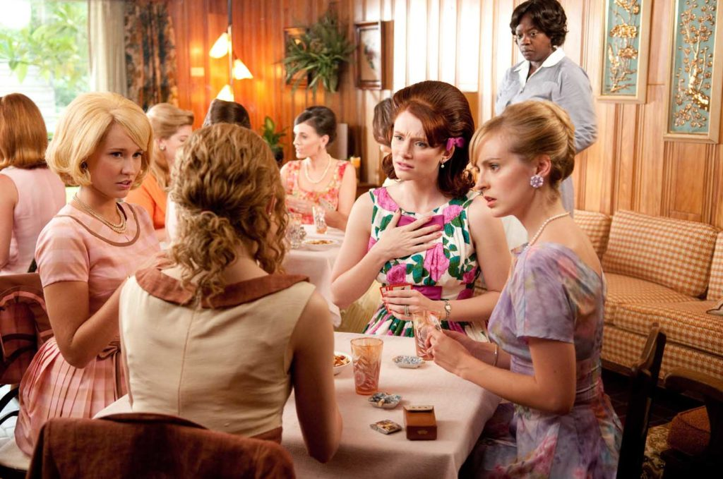 """""""THE HELP"""" TH-026R Skeeter Phelan (Emma Stone, back to camera) makes a remark that shocks her bridge-playing friends Elizabeth Leefolt (Ahna OÕReilly, seated right), (right to left) Hilly Holbrook (Bryce Dallas Howard) and Jolene French (Anna Camp), while Aibileen Clark (Academy Award¨ nominee Viola Davis, far right) looks on, in DreamWorks PicturesÕ inspiring drama, ÒThe Help,Ó based on the New York Times best-selling novel by Kathryn Stockett. ÒThe HelpÓ is written for the screen and directed by Tate Taylor, with Brunson Green, Chris Columbus and Michael Barnathan producing. Ph: Dale Robinette ©DreamWorks II Distribution Co., LLC. ÊAll Rights Reserved."""