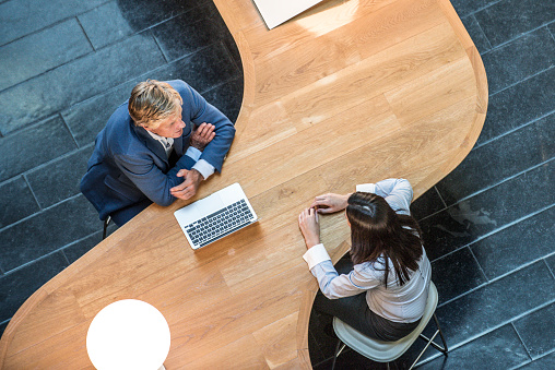 Two business people in meeting at curved desk overhead view