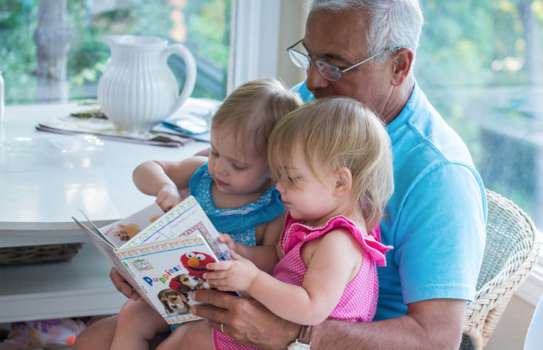 grandfather-reading-a-story-for-twin-girls