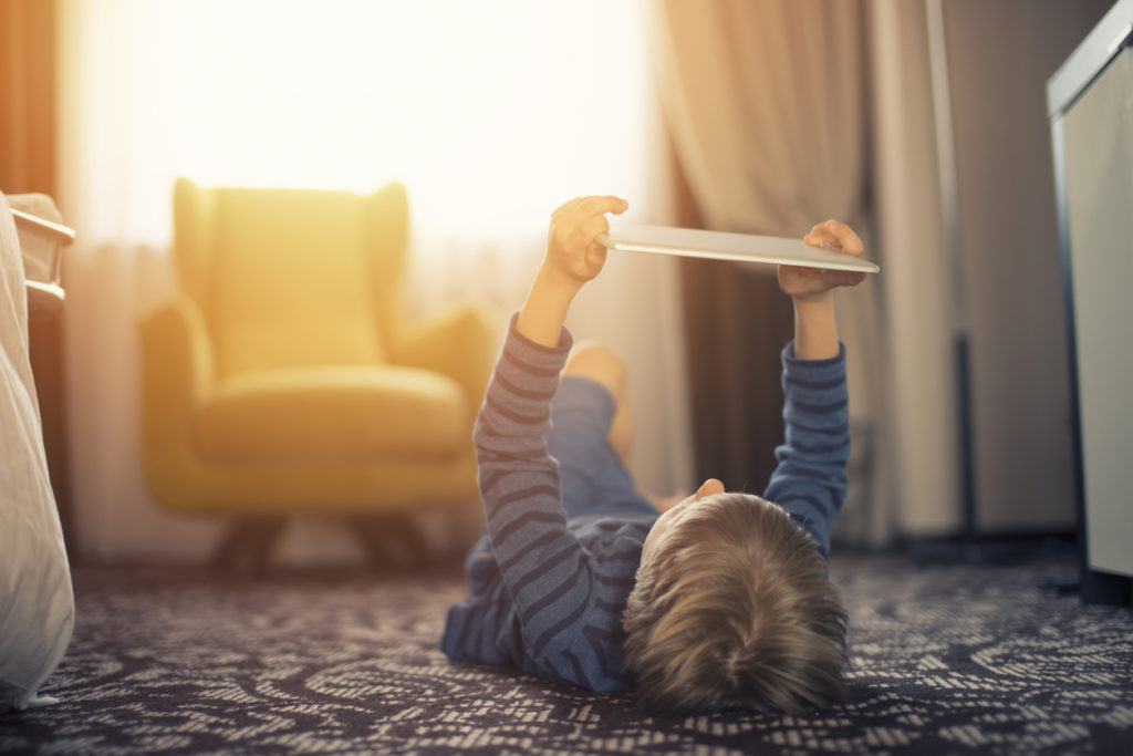 Little boy lying on the back on the floor playing games on digital tablet.