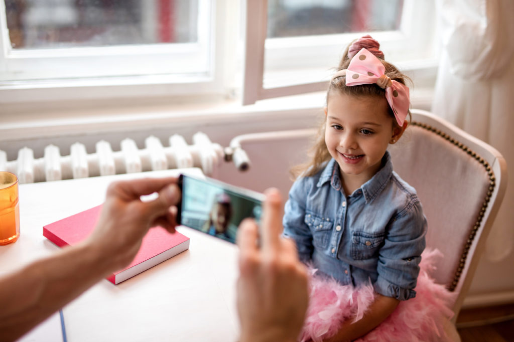 Cute little girl at home being photographed with smart phone.