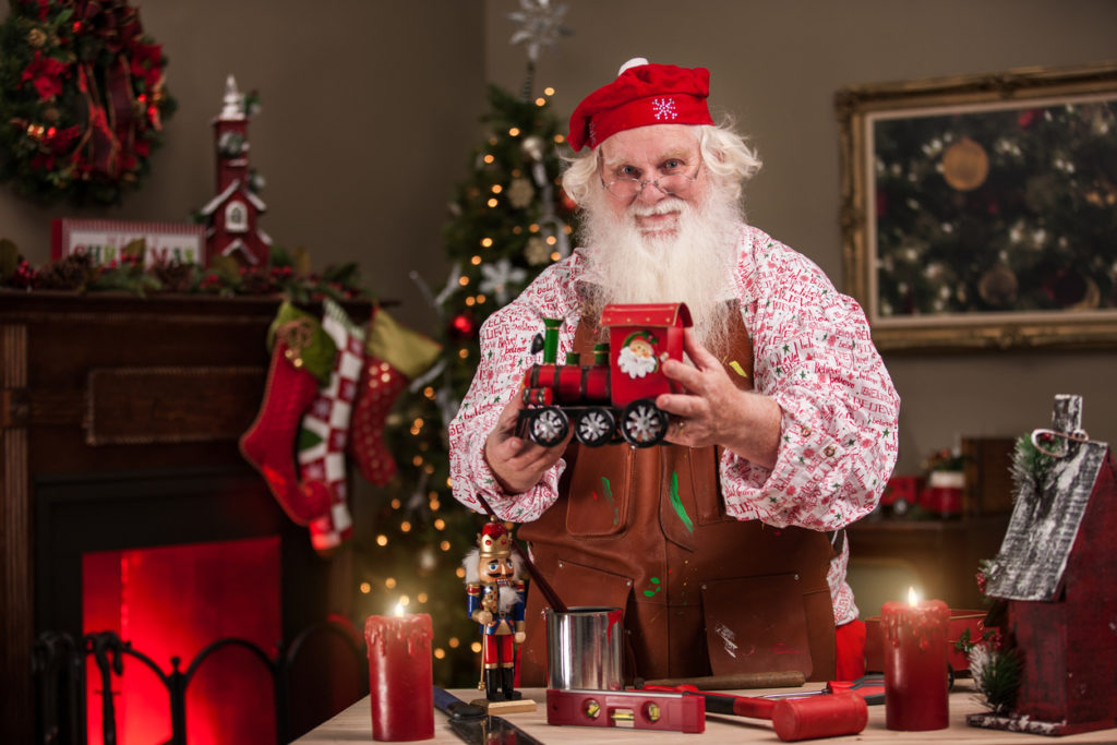 Santa Claus stands at his workbench, wearing a leather apron and proudly holding a toy train that he built by hand in his workshop.