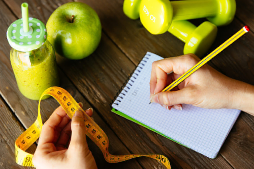 Woman writing nutrition diet and fitness workout routine. Healthy green detox, apple and dumbbells for slimming down concept. Female hands with measuring tape for checking weight loss.